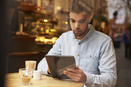 Man Viewed Through Window Of Caf? Using Digital Tablet