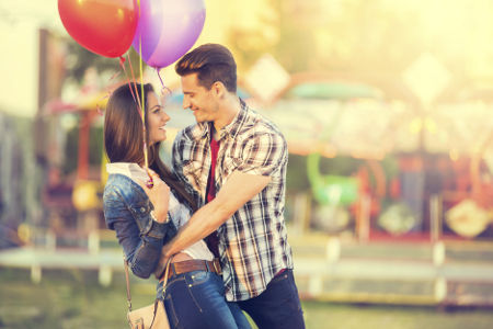 romantic couple in embrace looking at each other with a carousel in the background
